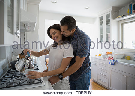 Affectionate couple pouring coffee at stove in kitchen - Stock Photo