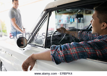 Father and son with vintage car in garage - Stock Photo