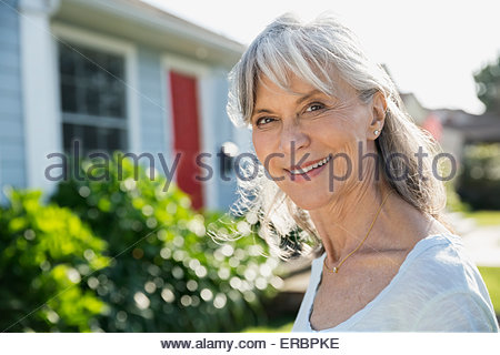 Portrait smiling senior woman in sunny front yard - Stock Photo