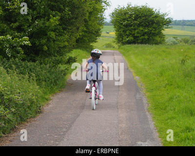 A young girl rides a bike on a country lane - Stock Photo