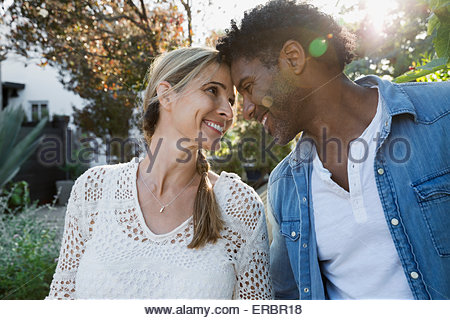 Affectionate couple smiling face to face outdoors - Stock Photo