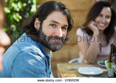 Portrait of confident man at patio table - Stock Photo