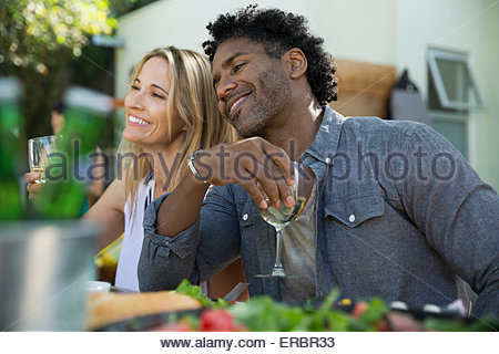 Smiling couple drinking wine at patio table - Stock Photo