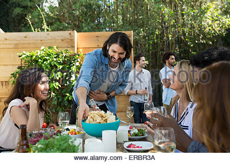 Friends eating and drinking at patio table - Stock Photo