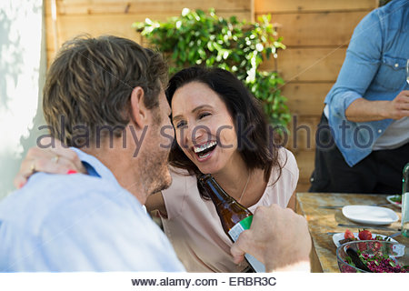Laughing couple face to face at patio table - Stock Photo