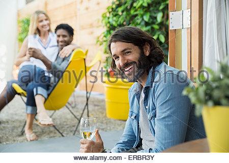 Portrait of smiling man drinking wine on patio - Stock Photo