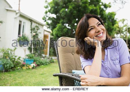 Portrait smiling enthusiastic brunette woman in backyard - Stock Photo