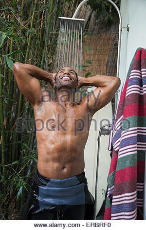 Smiling man in wet suit using outdoor shower - Stock Photo