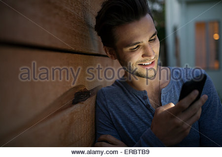 Man texting with cell phone on dark patio - Stock Photo
