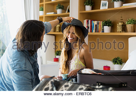 Man trying hat on woman near suitcase - Stock Photo