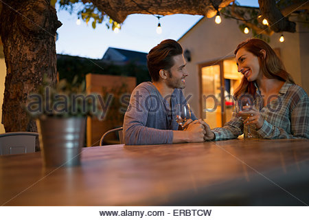 Affectionate couple drinking wine holding hands on patio - Stock Photo