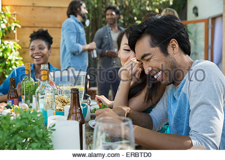 Woman whispering to laughing man at patio table - Stock Photo