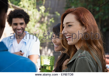 Smiling friends talking on patio - Stock Photo
