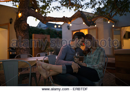 Affectionate couple relaxing drinking wine on patio - Stock Photo