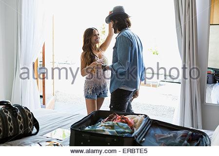 Woman trying hat on man window near suitcase - Stock Photo