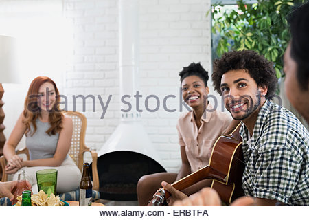 Friends hanging out playing guitar in living room - Stock Photo