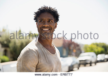 Smiling man curly black hair on sunny street - Stock Photo