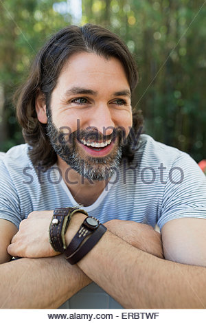 Close up portrait smiling bearded man looking away - Stock Photo