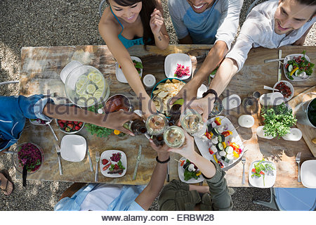 Overhead view friends toasting wine glasses patio table - Stock Photo