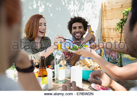 Woman serving friends at patio table - Stock Photo