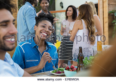 Smiling woman eating with friends at patio table - Stock Photo