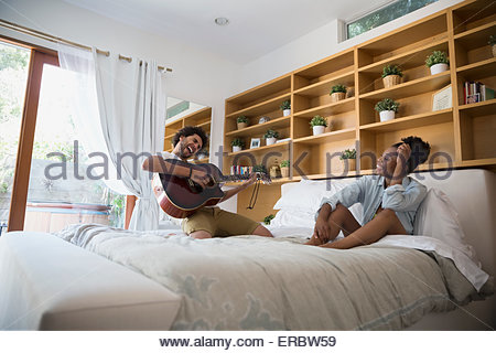 Enthusiastic man playing guitar for girlfriend on bed - Stock Photo