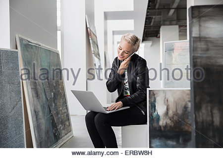 Art dealer with laptop talking on cell phone - Stock Photo