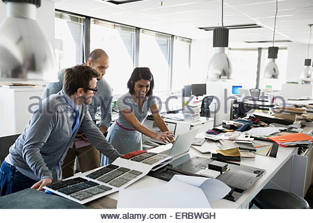Interior designers with swatches working at laptop - Stock Photo