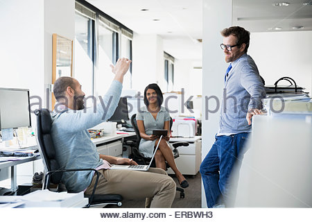 Businessman gesturing and explaining to co-workers office - Stock Photo