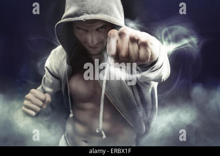 Hooded muscular boxer punching an enemy - Stock Photo