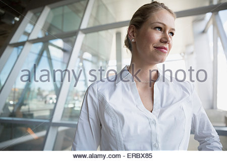 Smiling blonde businesswoman with blonde hair looking away - Stock Photo