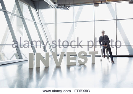 Portrait businessman sitting next to 'Invest' letters - Stock Photo