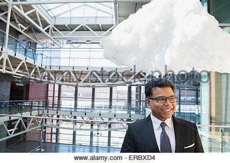 Cloud over smiling businessman in atrium - Stock Photo