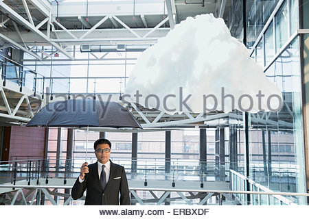 Portrait businessman with umbrella under cloud in atrium - Stock Photo