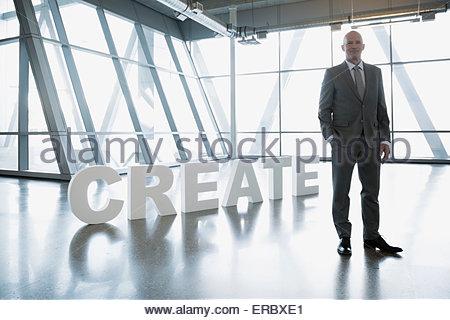 Portrait of confident businessman next to 'Create' letters - Stock Photo