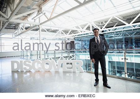 Portrait confident businessman next to 'Discover' text atrium - Stock Photo