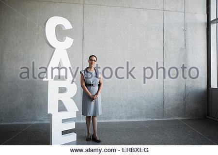 Portrait female doctor next to 'Care' letters - Stock Photo