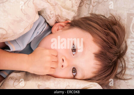 2 - 4 year old Caucasian child, boy. In bed, head on pillow with fingers in mouth, looking at viewer, anxious expression - Stock Photo