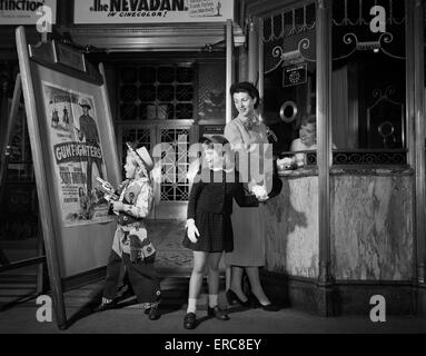 1950s MOTHER TAKING KIDS TO MOVIES BUYING TICKETS TO A WESTERN BOY WEARING COWBOY COSTUME - Stock Photo