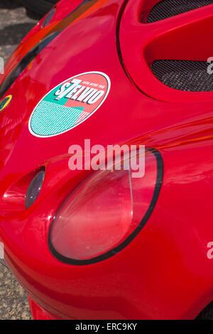 Red Lotus Sports Car light detail with Lotus Alpine Tour s7elvio sticker on front - Stock Photo