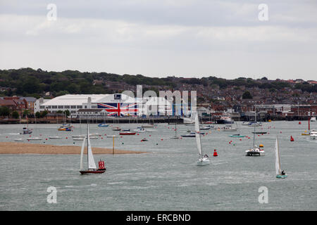Yachts sail past Venture Quays in Cowes on the Isle of Wight which has the world's largest Union Flag painted on - Stock Photo