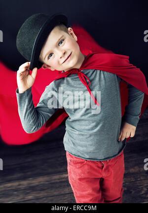 Little elegant magician boy touching his top hat - Stock Photo