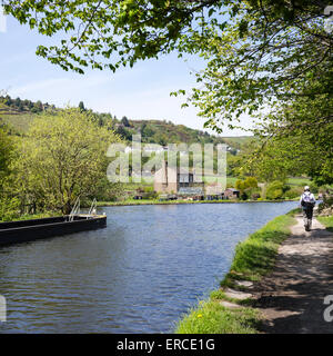 A walker on the towpath of the historic Leeds Liverpool Canal NE of Marsden, Yorkshire, England - Stock Photo