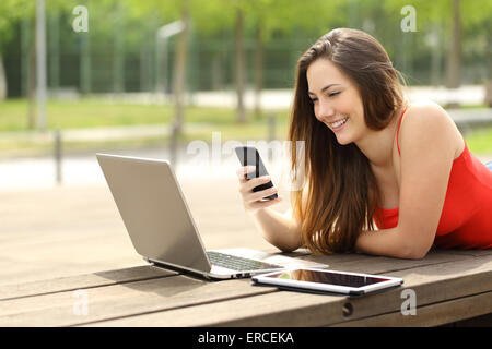 Happy girl using a laptop and smart phone lying in a bench in a park - Stock Photo