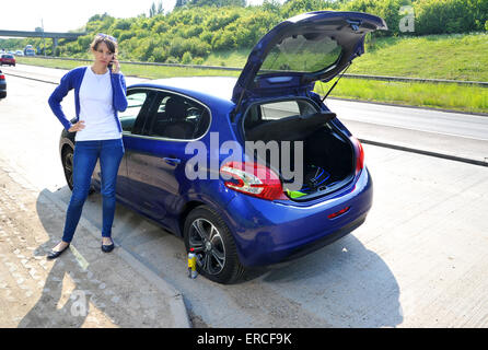 Woman with car puncture using a can of tyre sealant and inflater - Stock Photo