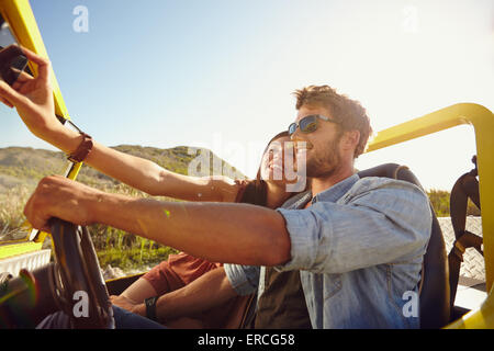 Couple on road trip, man driving a car and woman taking selfie on her mobile phone. - Stock Photo