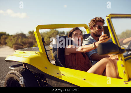 Excited happy couple enjoying road trip in their car. Man driving the car young woman taking a selfie from her mobile - Stock Photo