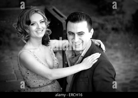 Newly wed couple laughing outdoor on a summer day. - Stock Photo