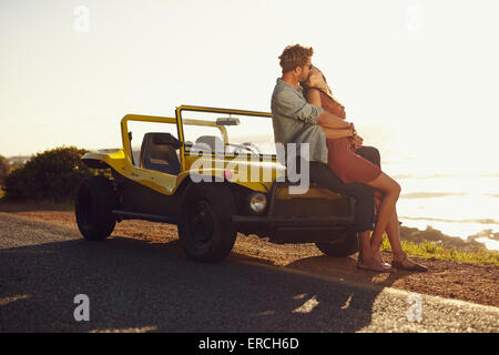 Romantic young couple sitting on hood of their car and kissing. Young couple sharing a passionate kiss on road trip. - Stock Photo