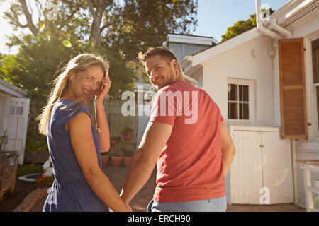 Rear view shot of a young couple taking a walk around their house holding hands. Loving young couple outdoors in - Stock Photo